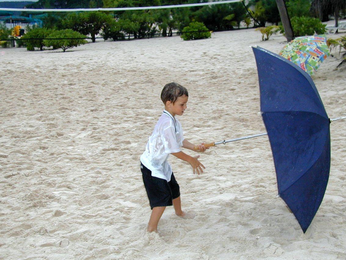 Boy Learning to Use Umbrella